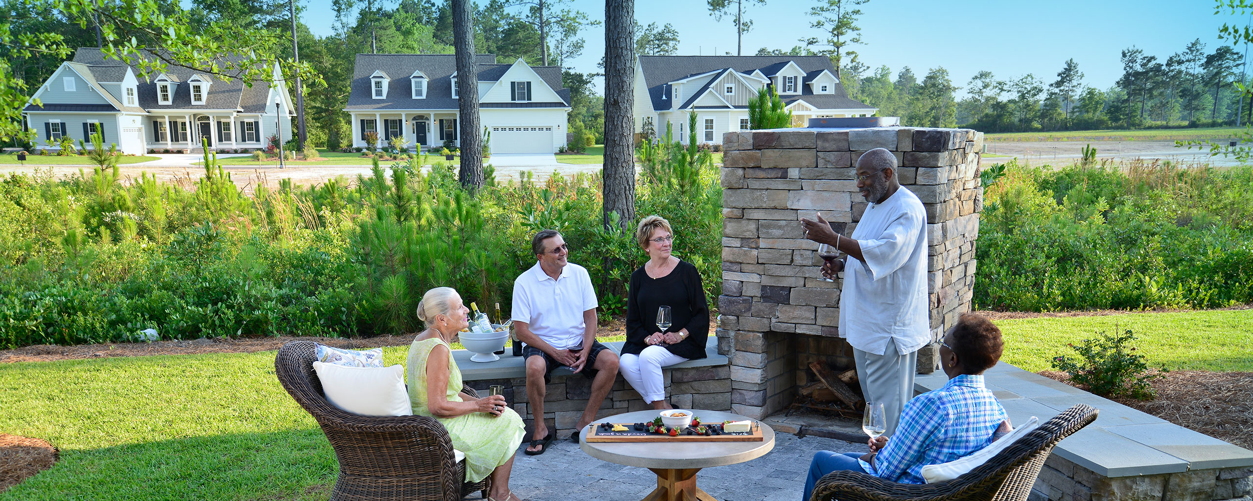 Neighbors having drinks near outside fireplace