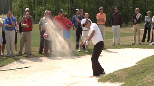 Golfer chipping out of the bunker