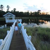 Couple walking to gazebo over a pond