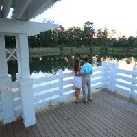 Couple watching the sun set from a gazebo over a pond