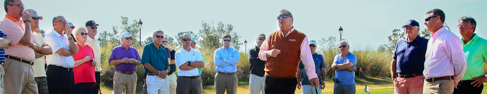 Fuzzy Zoeller talks with residents on a green during a visit.