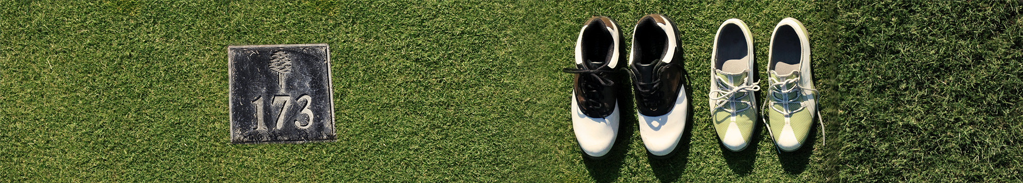 Two pair of golf shoes on the grass next to a yardage marker