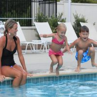 Children jumping into the pool next to their mom