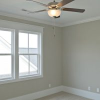 Ceiling fan and large windows in a bedroom of the Portsmith at Brunswick Forest