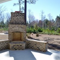 A brick fireplace on the partially covered pation of the Kensington at Brunswick Forest