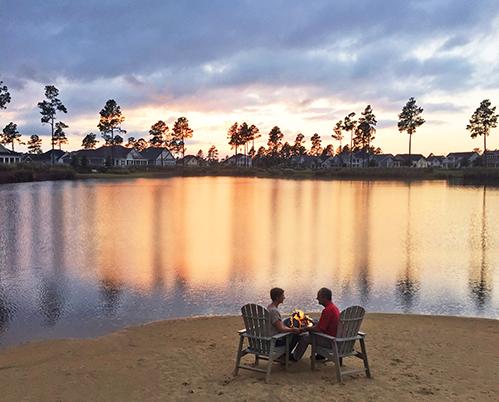 Couple enjoying Hammock Lake by a fire pit around sunset