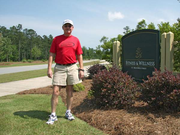 Ed Fore standing by entrance sign of the fitness & Wellness center at Brunswick Forest