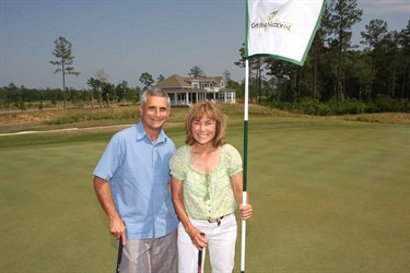 Sandy and Heidi Ergas standing on the green at Cape Fear National