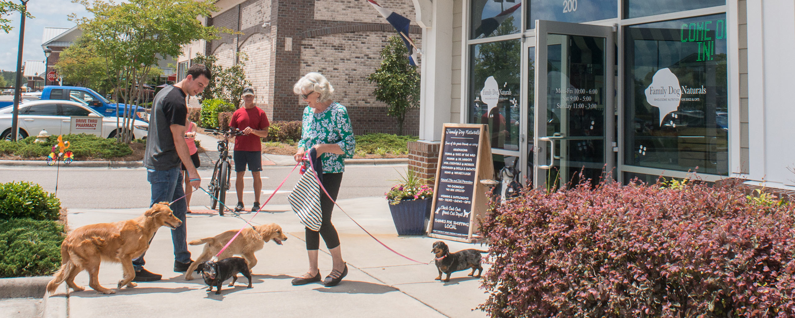 Dogs and their owners outside of Family Dog Naturals